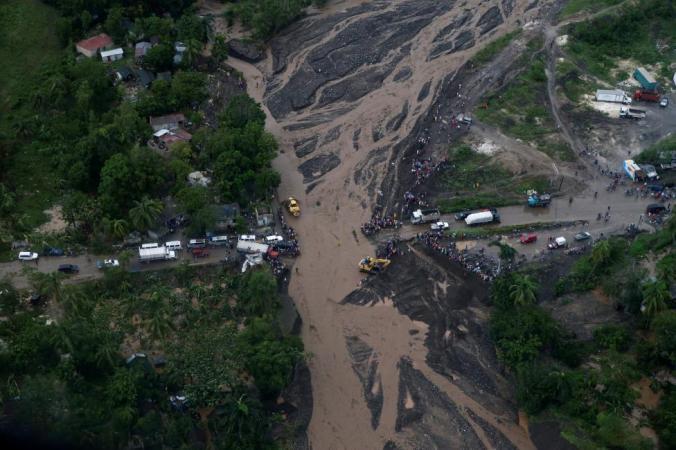 People gather next to a collapsed bridge after Hurricane Matthew passes Petit Goave, Haiti