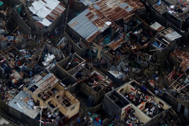 People walk next to destroyed houses after Hurricane Matthew passes Jeremie, Haiti