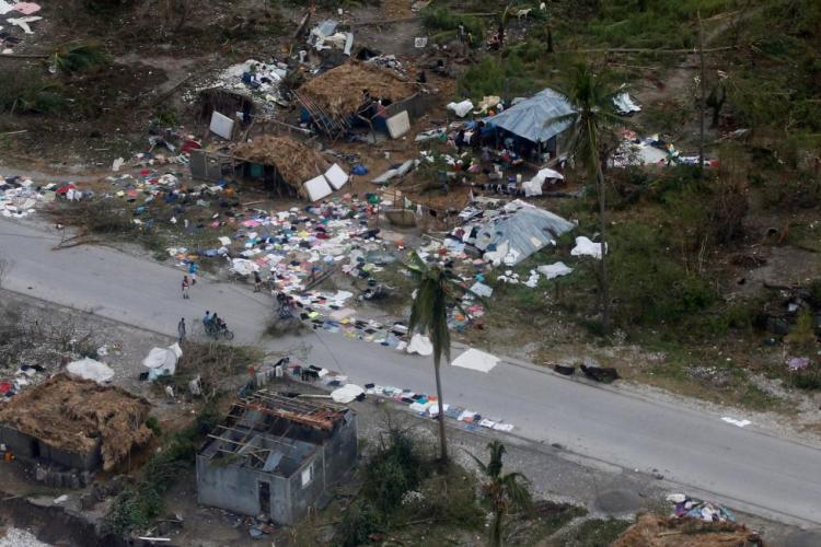 People walk down the street next to destroyed houses after Hurricane Matthew passes Jeremie, Haiti
