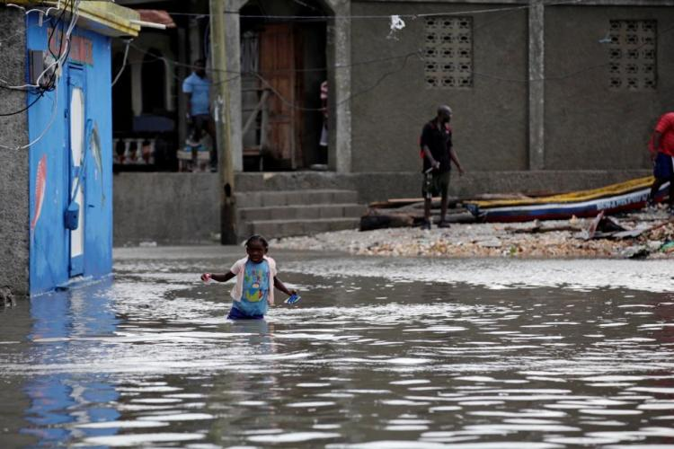 A girl walks in a flooded area after Hurricane Matthew in Les Cayes